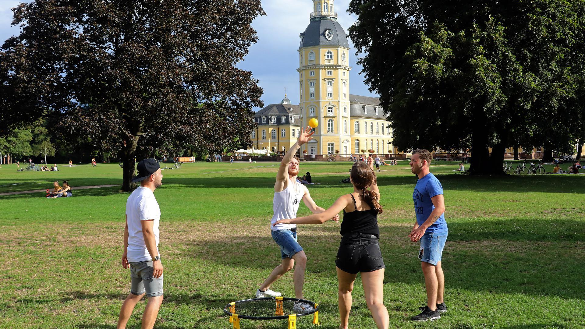 Vier junge Leute spielen vor dem Karlsruher Schloss Spikeball.