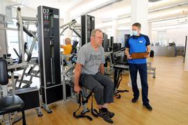Daniel Schwarz rechts begleitet einen Kunden beim Training an einem Gerät
