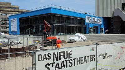 """Baustelle des Badischen Staatstheaters, im Vordergrund ein Schild mit der Aufschrift """"Das neue Staatstheater"""""""