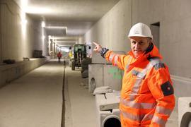 Ein Mann mit einer orangen Jacke und einem weißen Helm deutet in den Autotunnel unter der Kriegsstraße hinein.