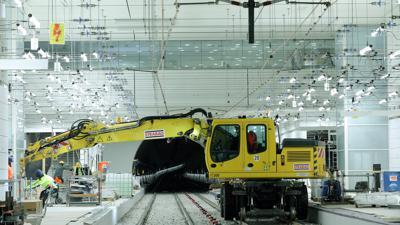 """Baubahn im Untergrund:  Der gelbe Rollbagger fährt die U-Strab-Station """"Europaplatz"""" an.  Das Lichtgespinst in der unterirdischen Halle sorgt schon für Helligkeit. Straßenbahnen rollen dort erst im April, vorerst zur Probe."""
