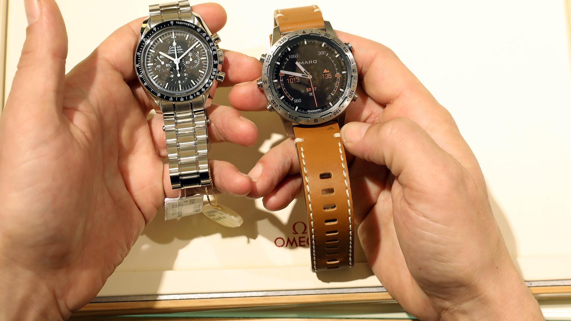 Ein Mann hält eine Smartwatch und eine klassische Armbanduhr in der Hand.