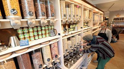 Eine Regalwand im Unverpackt-Laden in Karlsruhe. Ein Kunde holt lose Cerealien aus einem Glasbehälter.