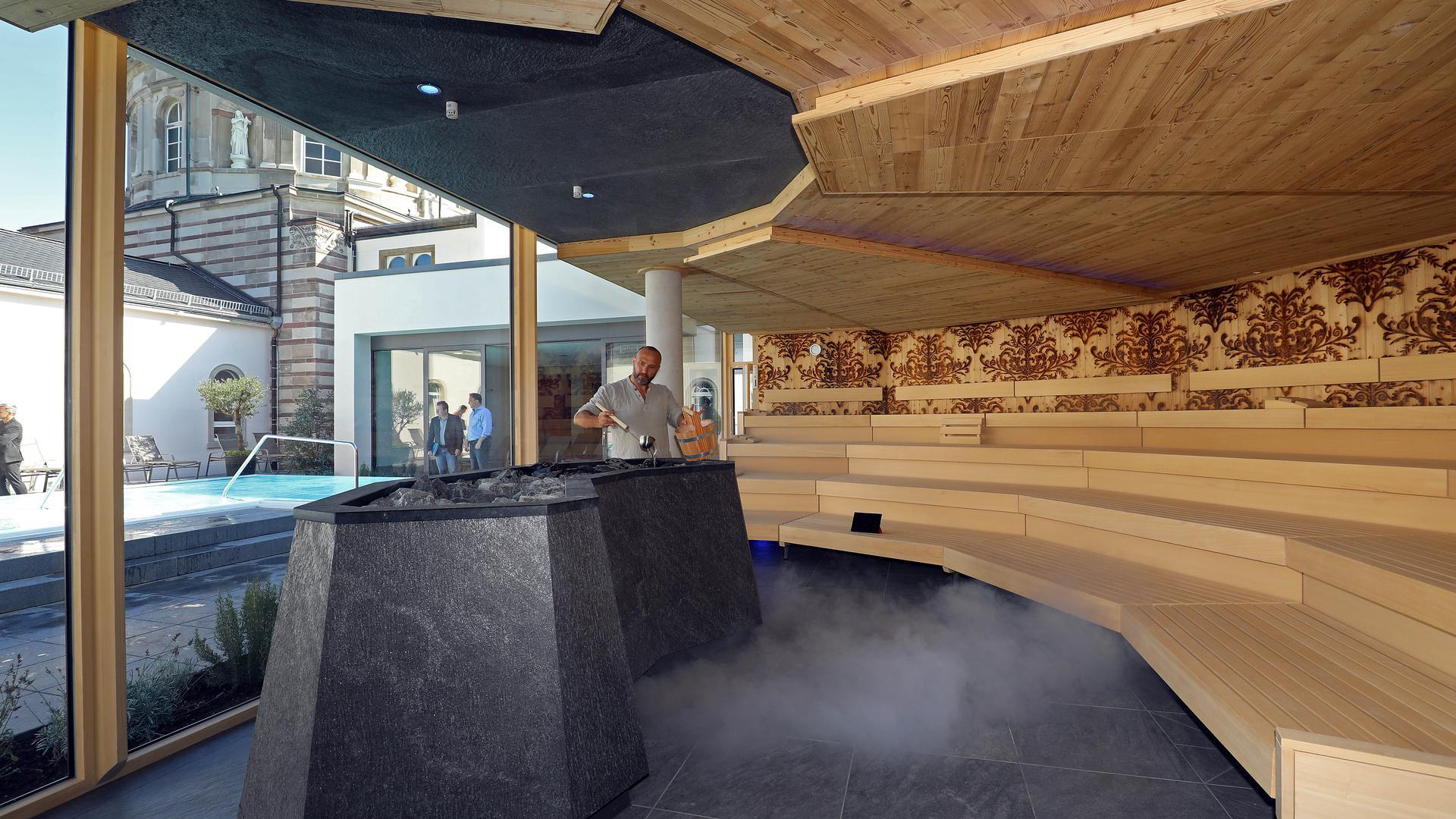 Saunameister in einer Sauna beim Aufguss.