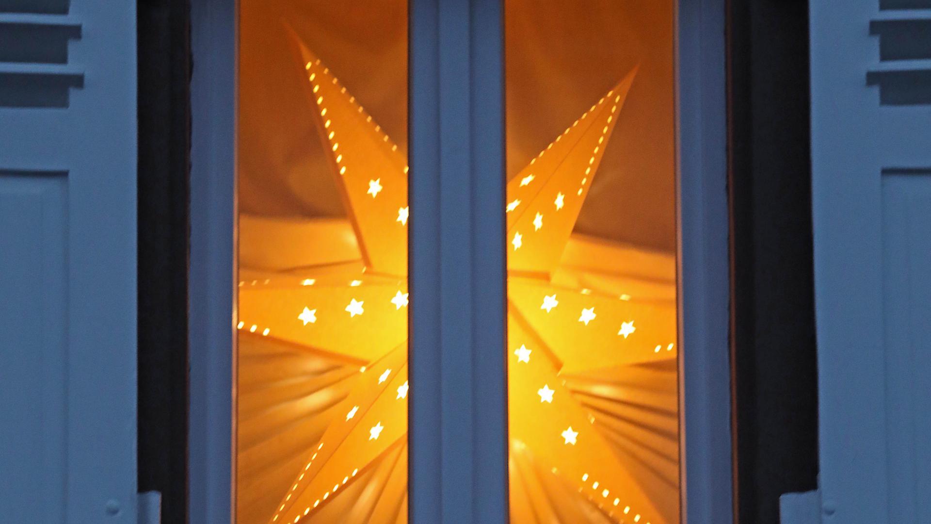 Ein gelber Weihnachtsstern leuchtet in einem dekorierten Fenster.
