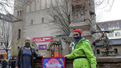 Symbol der Hoffnung: Pfarrerin Lara Pflaumbaum (rechts) und Künstlerin Gudrun Roth brachten das Friedenslicht an den Indianerbrunnen.