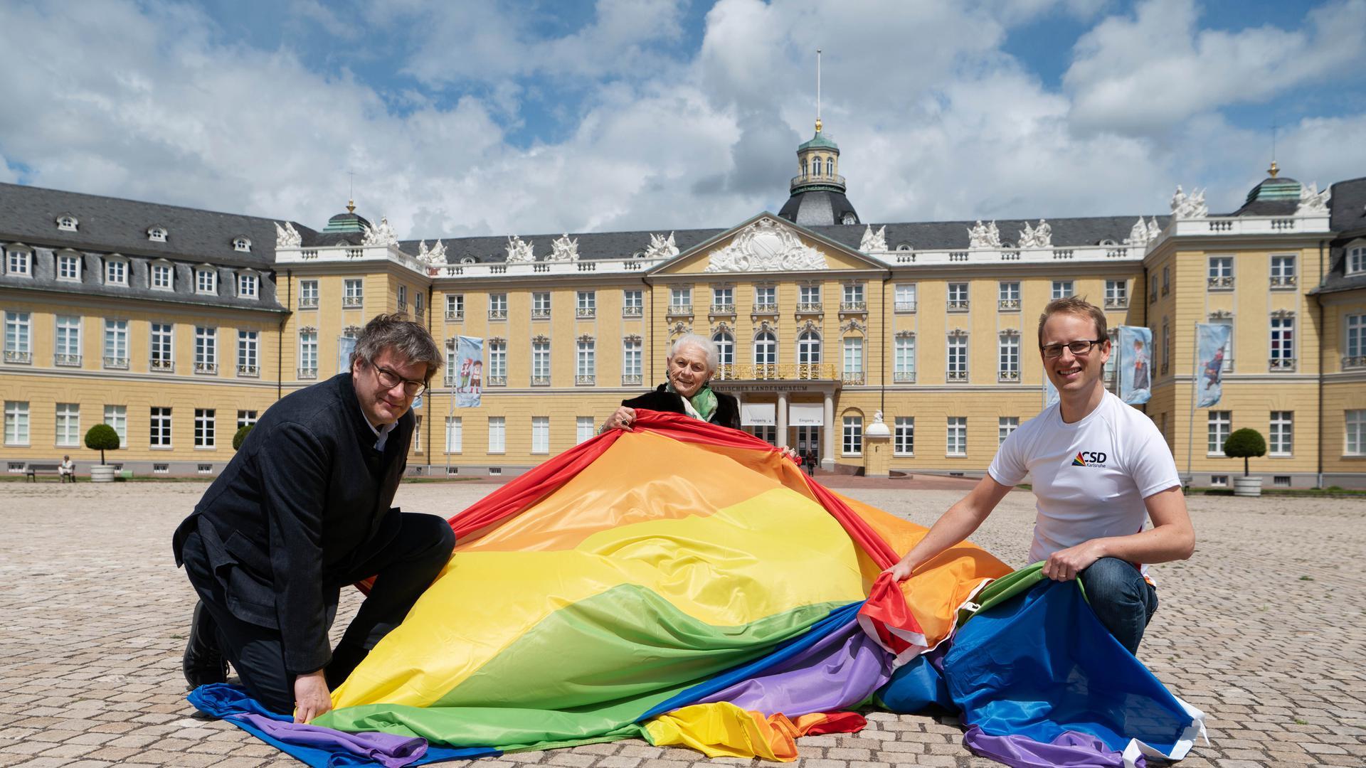 Am 5. Juni hisst das Badische Landesmuseum wieder die Regenbogenflagge auf dem Karlsruher Schlossturm. Gerlinde Hämmerle (Mitte) ist Schirmherrin des diesjährigen Christopher Street Days und hier mit Museumsdirektor Eckart Köhne und CSD-Organisator Karsten Kremer zu sehen.