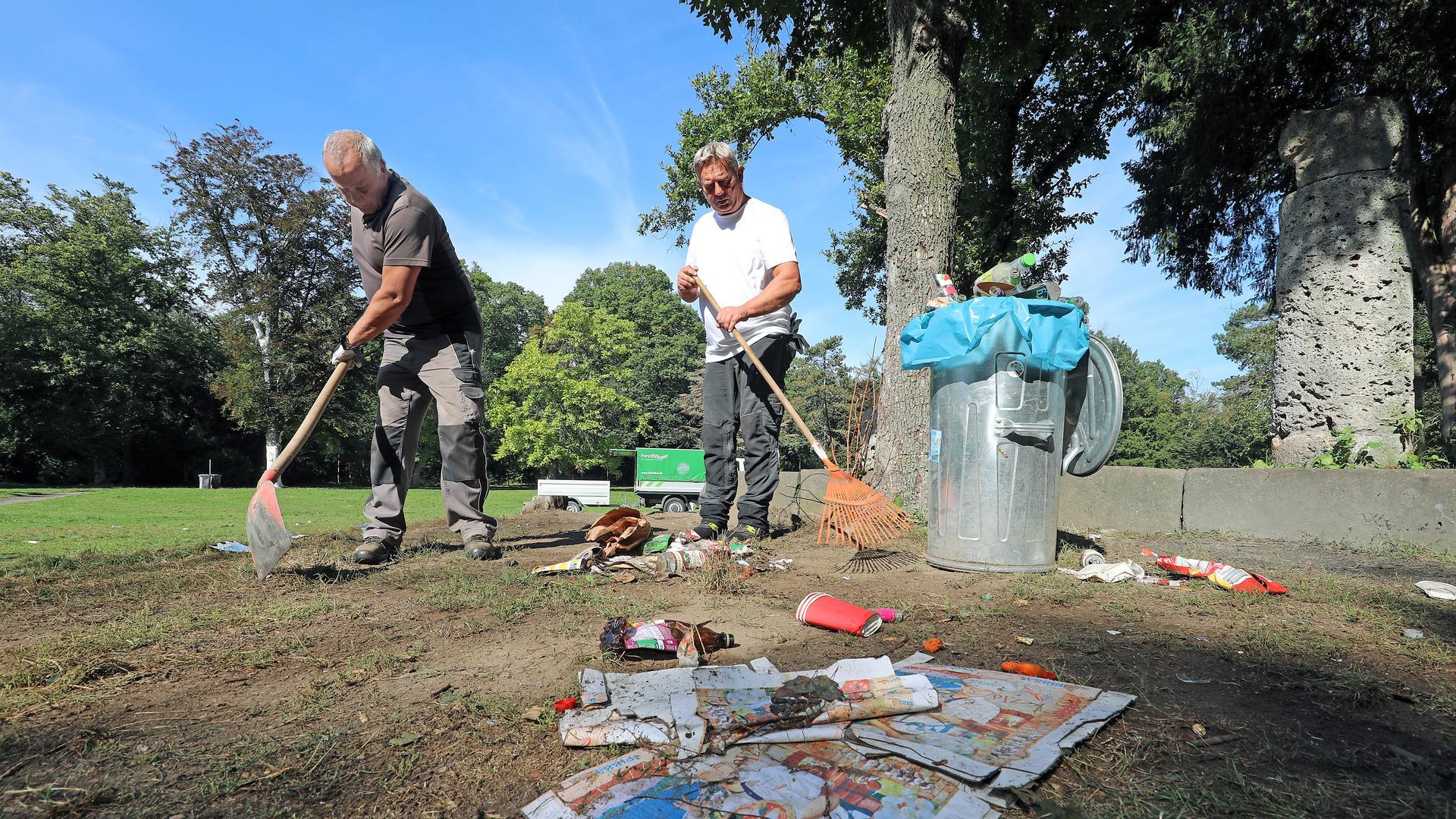 Wojciech Bebenek und Michael Gurnik sammeln mit Rechen und Schaufel Müll im Fasanengarten