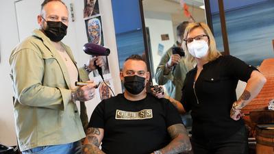 Geschäftsführer Manuel Mayer, Inhaber Michael Marton und seine Frau Cristin auf dem Friseurstuhl im Tattoo-Studio Waikiki.
