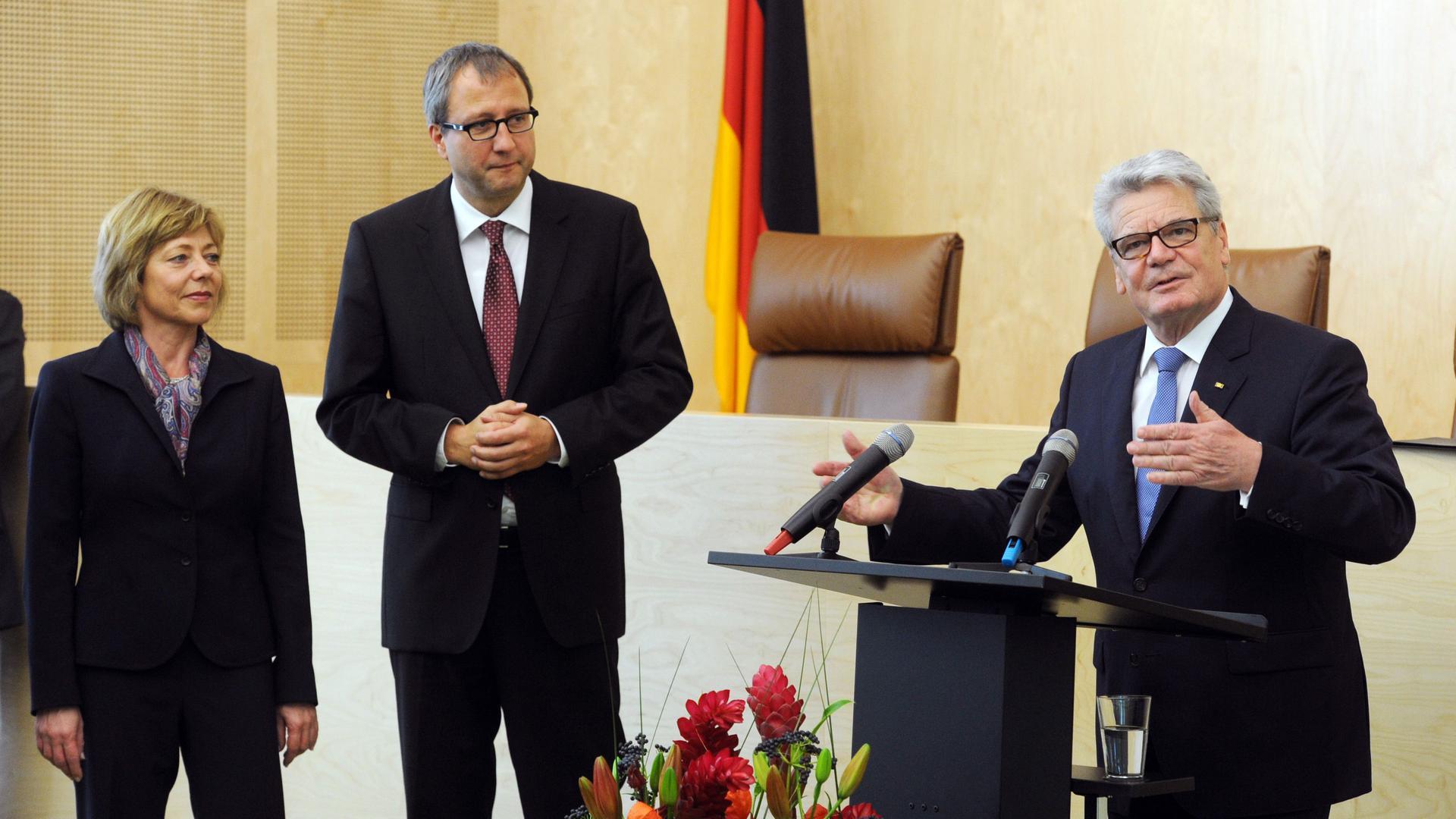 Bundespräsident Joachim Gauck (r) spricht am 18.10.2012 im Sitzungssaal des Bundesverfassungsgericht in Karlsruhe. Links steht Andreas Voßkuhle, Präsident des Bundesverfassungsgericht, sowie Daniela Schadt, Lebensgefährtin des Bundespräsidenten. Anlass ist der Antrittsbesuch von Gauck beim Verfassungsgericht. Foto: Uli Deck/dpa ++
