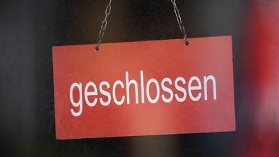"""In der Tür eines Geschäfts hängt ein Schild mit dem Schriftzug """"geschlossen""""."""