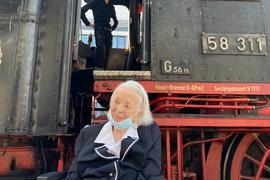 Aufeinandertreffen zweier Hundertjähriger: Gertrud Boos am Karlsruher Hauptbahnhof mit der Dampflok 58311.