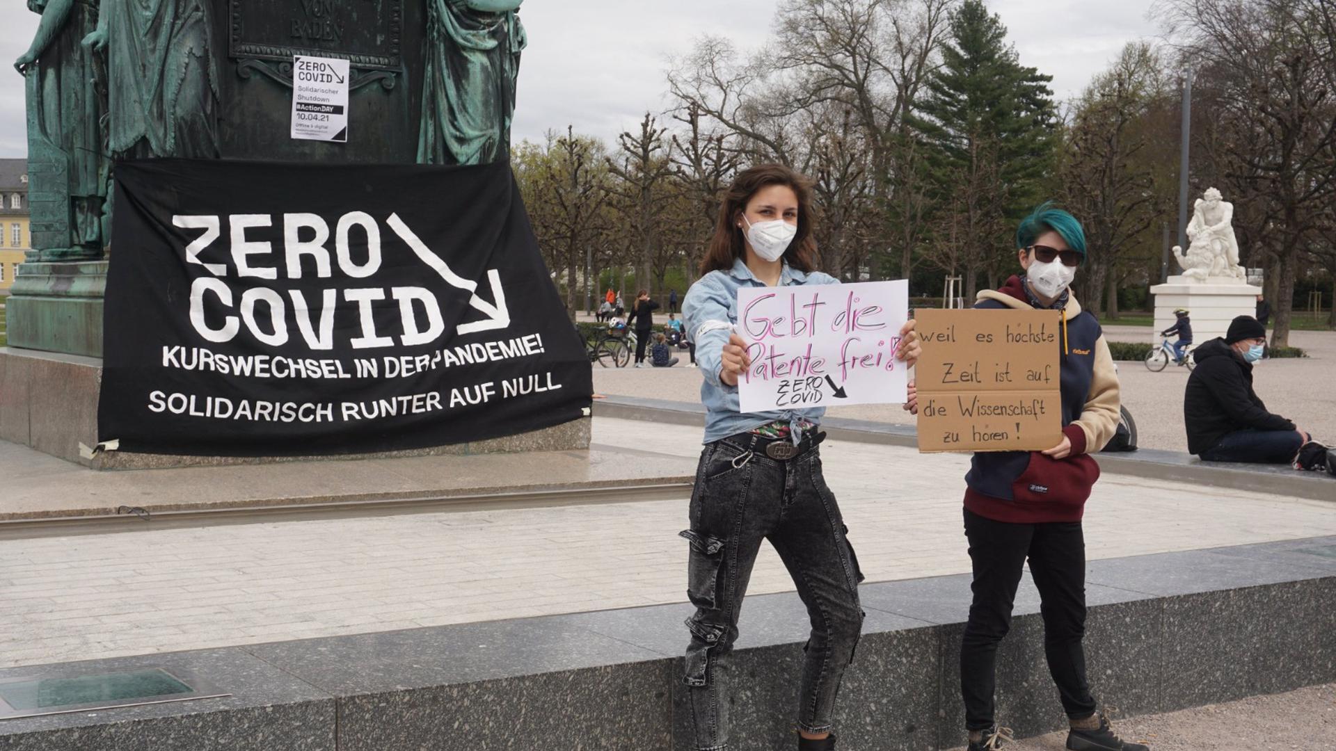 Christina Zacharias und Franziska Buresch (von links) demonstrieren vor dem Karlsruher Schloss für eine Freigabe der Corona-Impfstoffpatente und die solidarische, globale Bewältigung der Pandemie.