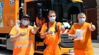 Drei Mitarbeiter der Müllabfuhr mit ihren Impfnachweisen