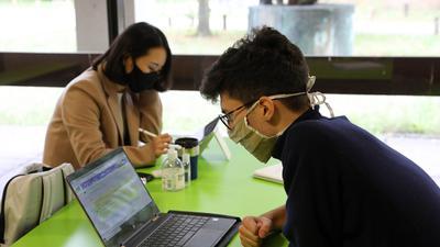 Zwei Studierende sitzen sich mit Masken am Laptop gegenüber.