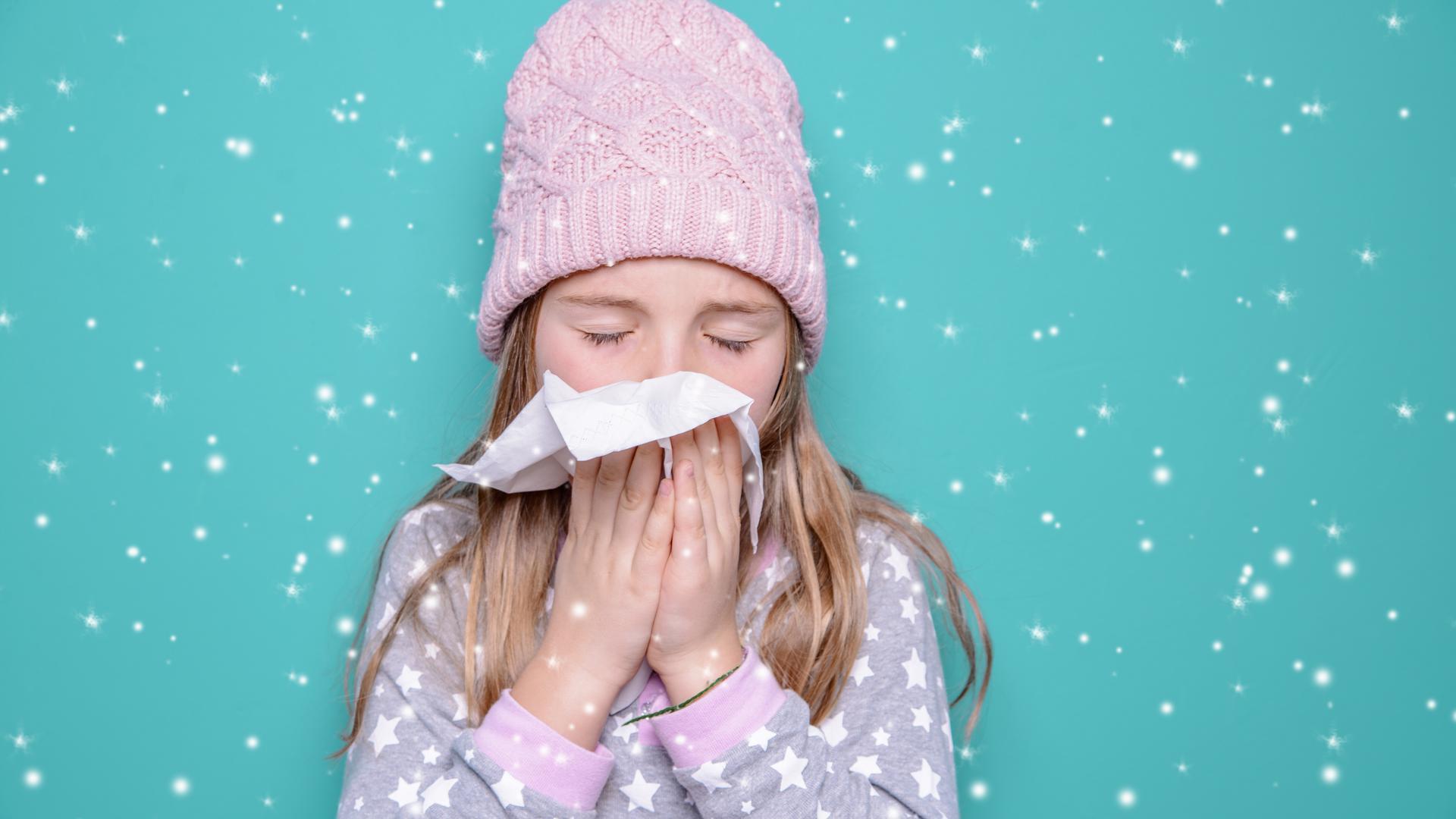 Mädchen mit Mütze schnäuzt sich in ein Taschentuch.