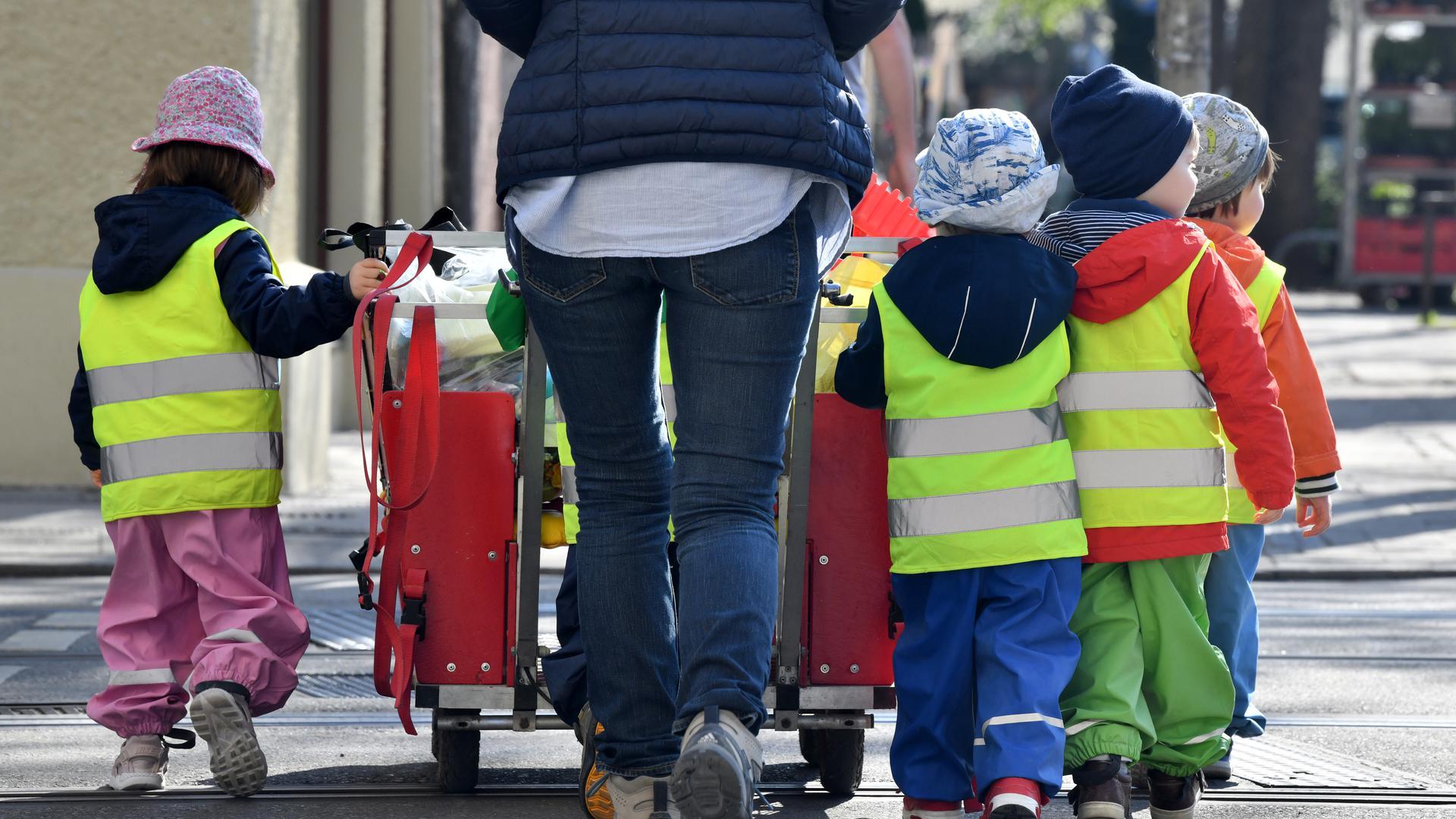 Ein Betreuerin läuft mit mehreren Kleinkindern über einen Bürgersteig.