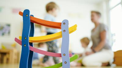 """Eine Erzieherin spielt in einer Kindertagesstätte hinter einer Rollbahn mit Kindern. (zu dpa """"Umfrage: Überlastung bei Kita-Personal, Unterforderung bei Kindern"""")"""