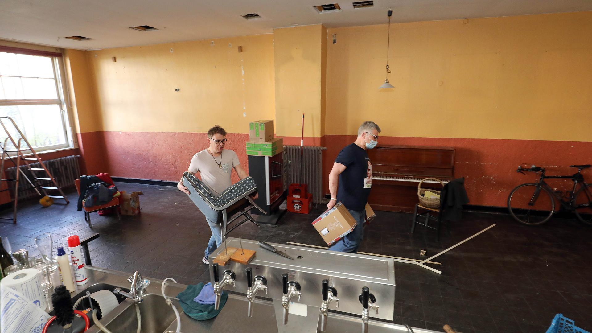 Uwe Link und ein Mitarbeiter räumen den Löwenbräukeller leer.