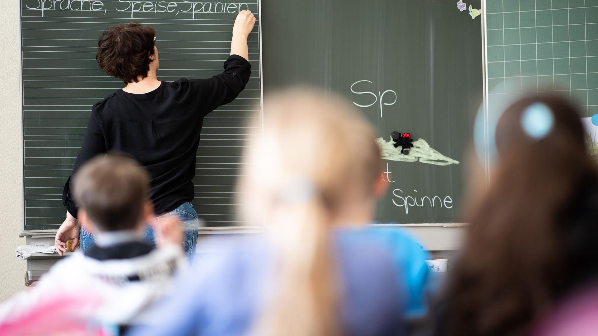 Eine Lehrerin schreibt in einer Schule an die Tafel.