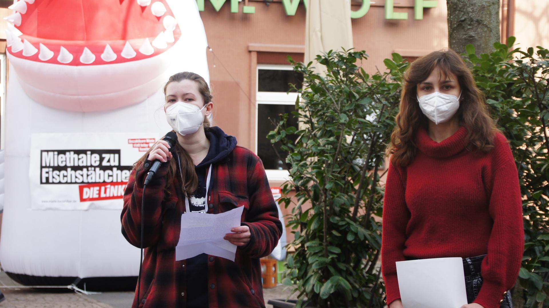Zwei Frauen, Anna Jahn und Christina Zacharias, mit Maske halten eine Rede.