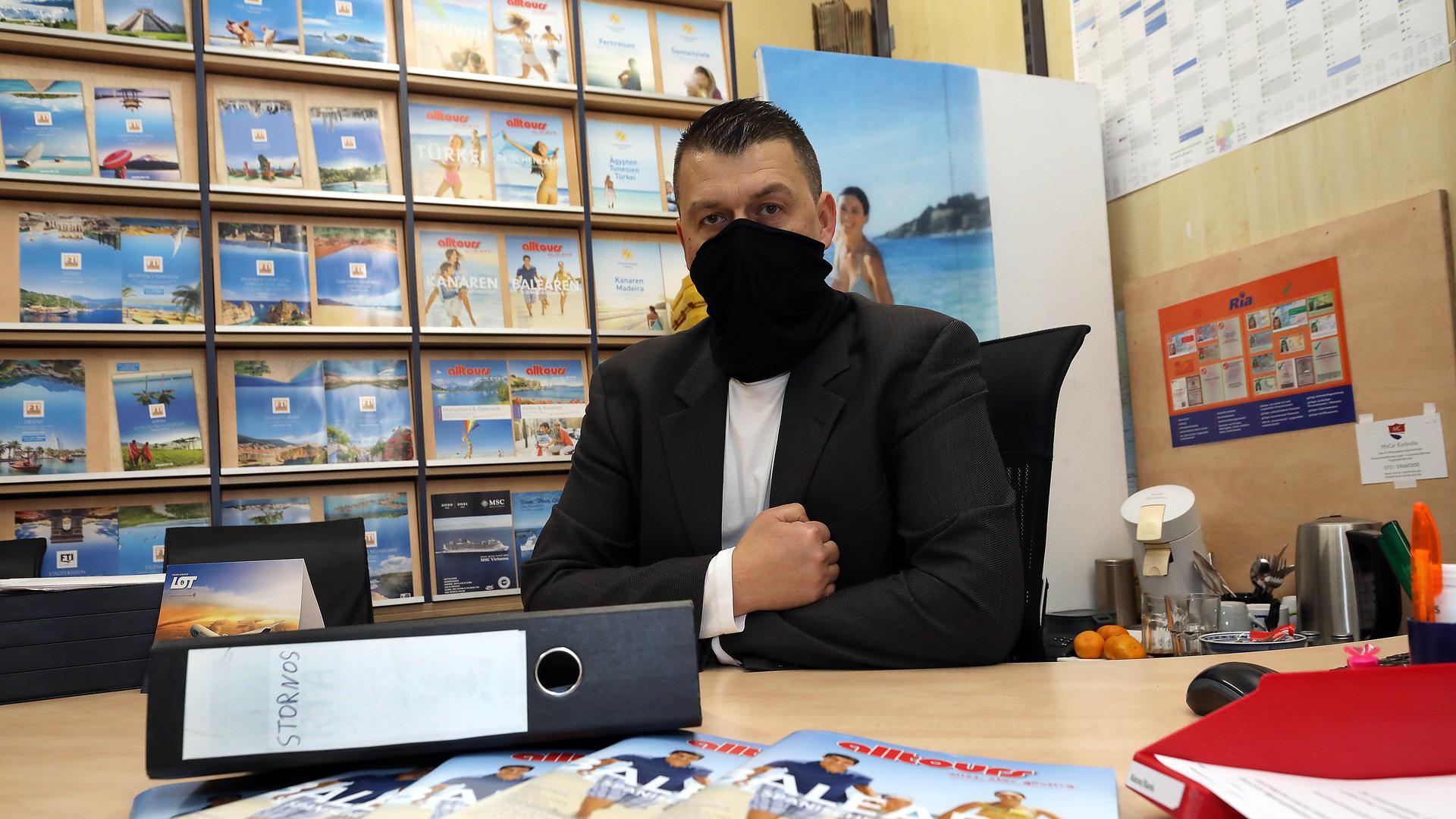 Reisebüro-Inhaber Andreas Döring an seinem Schreibtisch vor einem Ordner mit Stornierungen