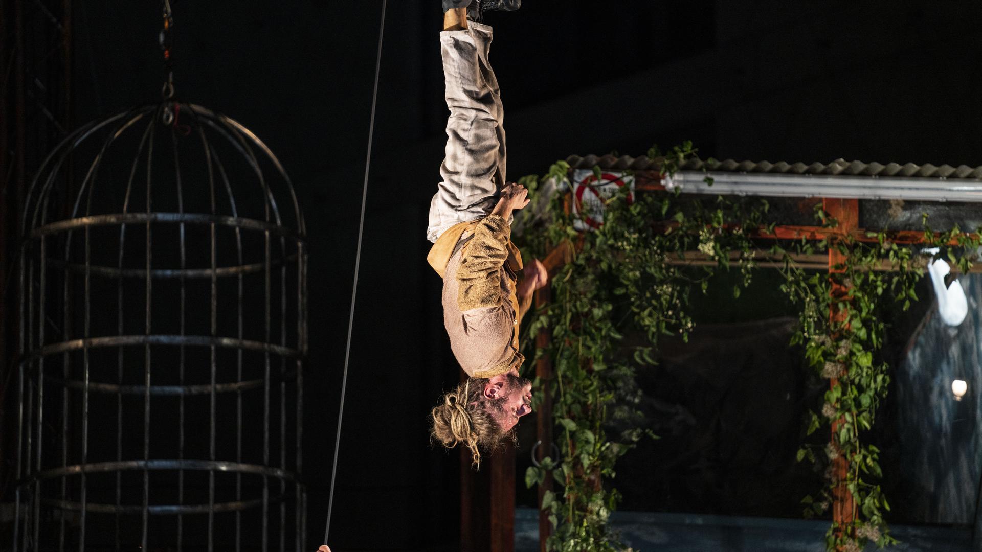 Ein Mann hängt kopfüber an einem Seil