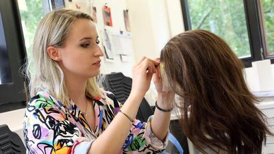 Maskenbildnerin Jasmin Müller knüpft Haare in eine Echthaarperücke.