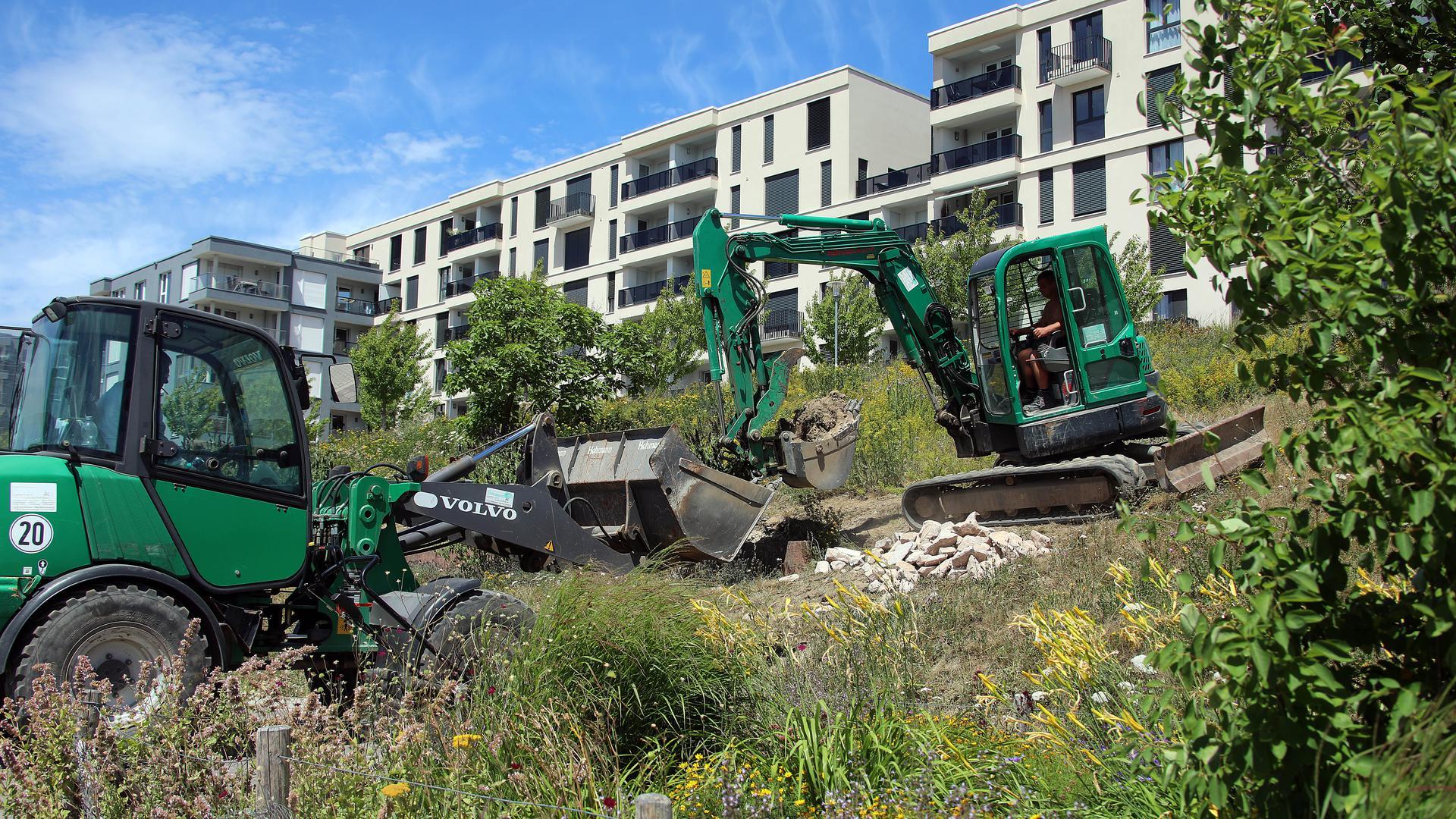 Arbeiter heben Gräben aus und füllen die Löcher mit Steinen und Sand.