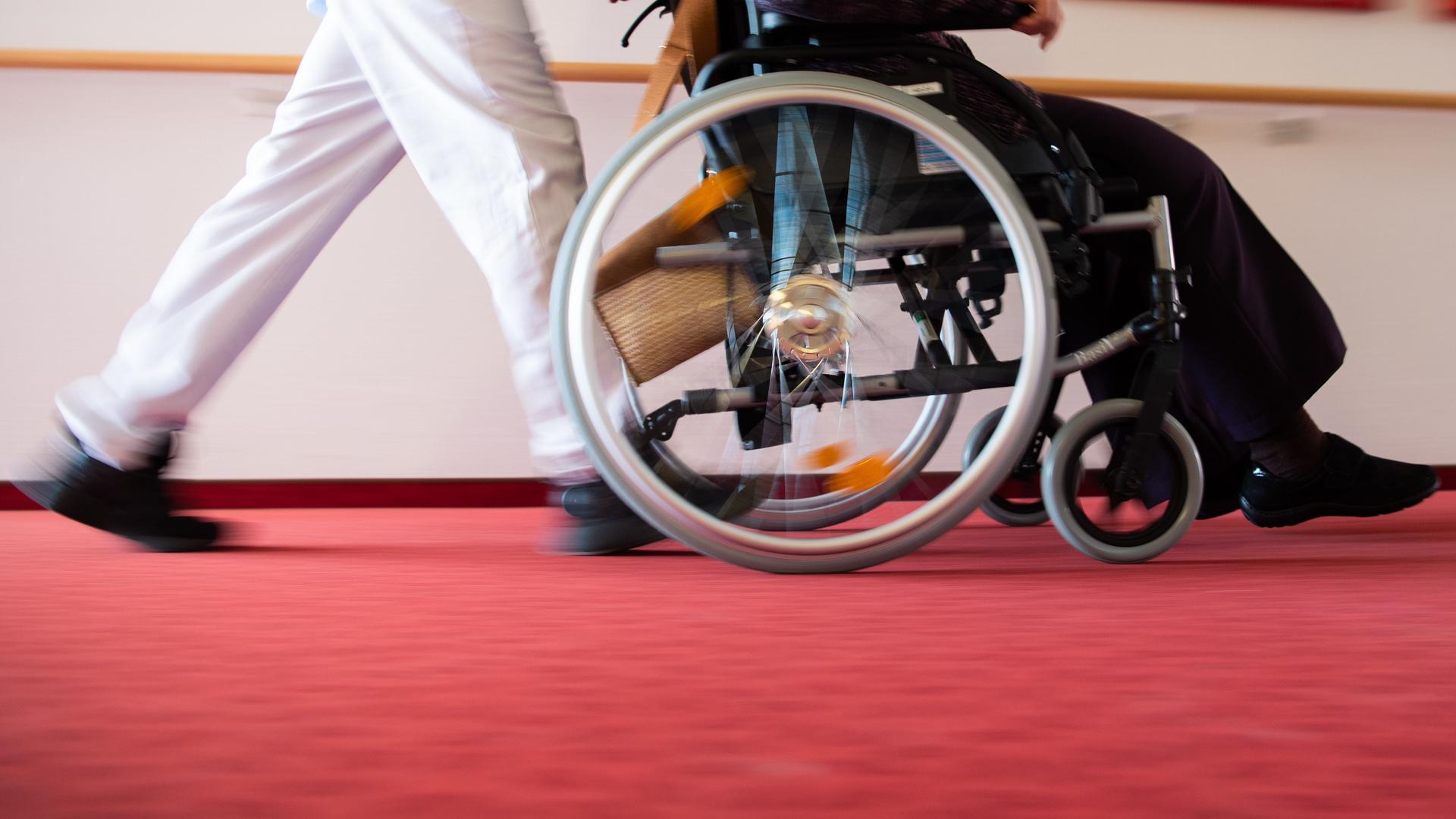 ARCHIV - 15.01.2020, ---: Ein Pfleger eines Pflegeheims schiebt eine Bewohnerin mit einem Rollstuhl. (zu dpa «Anwerbung ausländischer Pflegekräfte stockt wegen Corona») Foto: Tom Weller/dpa +++ dpa-Bildfunk +++ | Verwendung weltweit