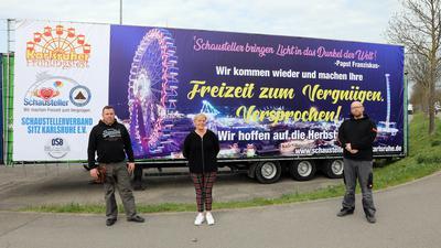 Robert und Susanne Filder sowie Willy Krusig Junior vor dem Plakat der Schausteller