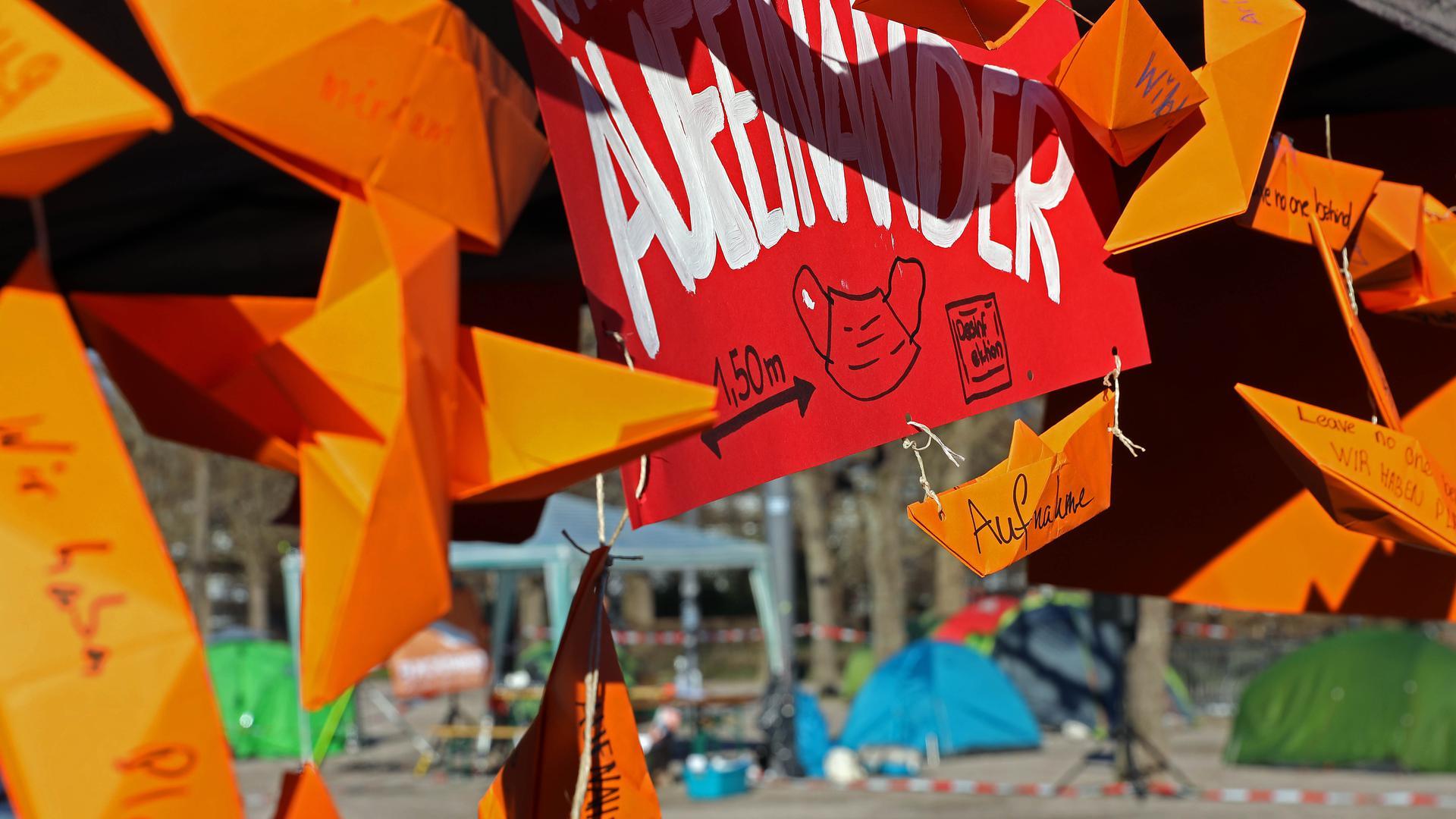 Orangene Papierboote im Vordergrund, Zelte im Hintergrund