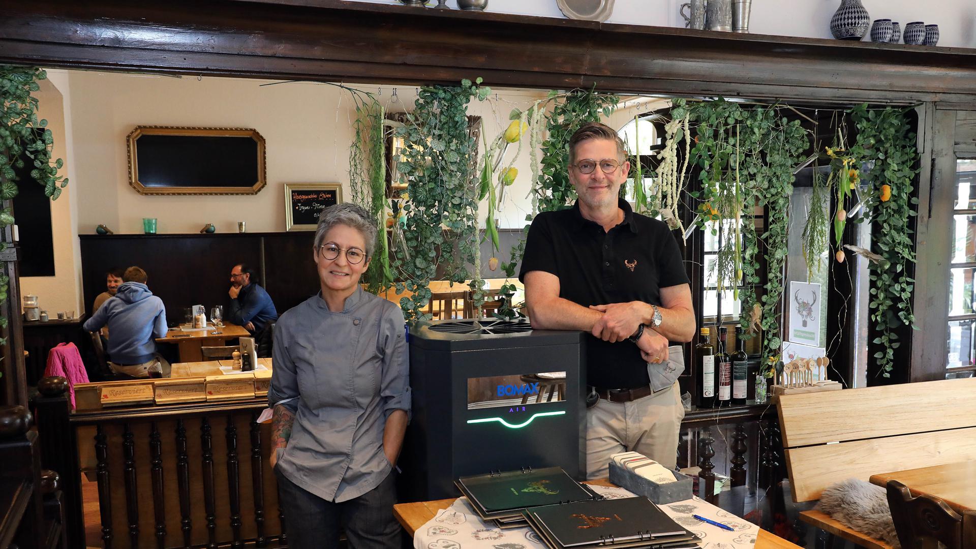 Denise Bender und Volker Rathert im Gasthaus Gutenberg neben einem Luftfilter.