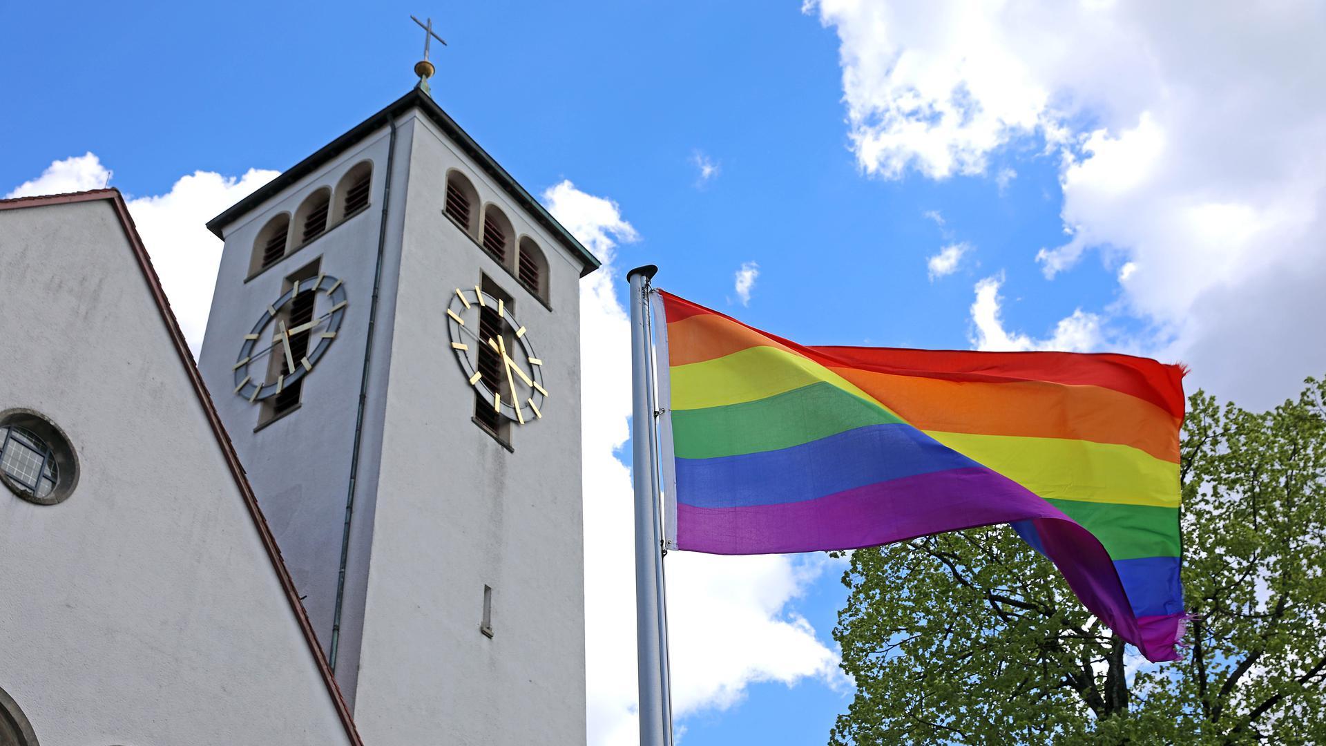 Eine Regenbogen-Fahne weht vor Christkönig in Rüppurr