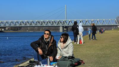 Fabienne und Philip haben es sich am Rheinufer auf einer Picknickdecke gemütlich gemacht.