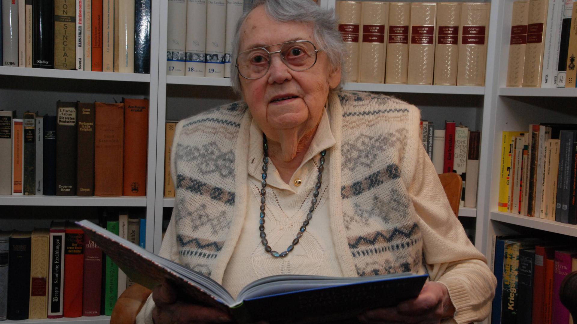 Eine ältere Frau mit Brille hält ein Buch.