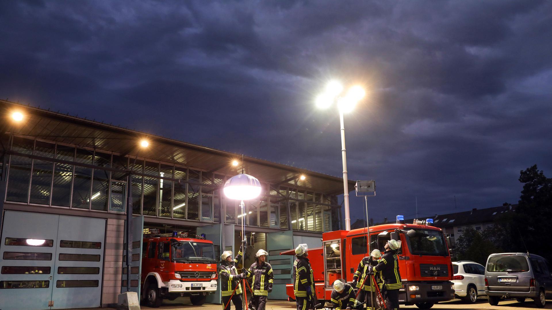 """Die Freiwillige Feuerwehr Durlach ist auf Beleuchtung spezialisiert. Dazu hat sie einen transportablen Lichtmast. Bis zu zwölf Meter schieben sich sieben Teleskopmast-Segmente über dem Spezialfahrzeug in die Höhe. An der Spitze strahlen vier stufenlos schwenkbare Scheinwerfer, jeder groß wie eine Babybadewanne, ihr kühles Licht ab. """"Wenn wir am Ufer über den Rhein leuchten, wird es gegenüber hell"""", erklärt Feuerwehrmann Gregor Franke. Blendfrei ergänzt ein Leuchtballon die Ausstattung. Zwei Feuerwehrler können das alles bedienen, im Normalfall rücken dafür sechs aus."""