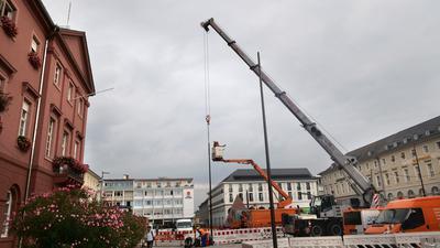 Eingepflanzt: 18 Masten von neun Metern Höhe werden auf dem Marktplatz installiert. Von ihren Spitzen sollen im Oktober Leuchten die dann aufgeräumte gute Stube der Fächerstadt in ein gutes Licht setzen.