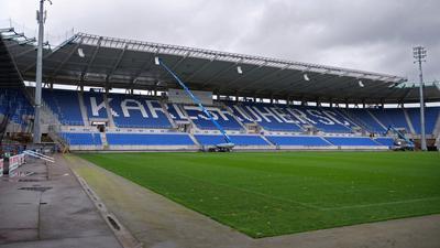 Klare Ansage: Die blauen und weißen Sitzschalen bilden auf der neuen Tribüne entlang des Adenauerrings den Schriftzug Karlsruher SC. Aktuell werden Lautsprecher in der Dachkonstruktion montiert.
