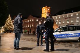 Kontrolle: Mitarbeiter des städtischen Ordnungsamts nehmen in der Silvesternacht die vereinzelten Passanten unter die Lupe, die entgegen der Verordnung noch spät auf der Straße sind.