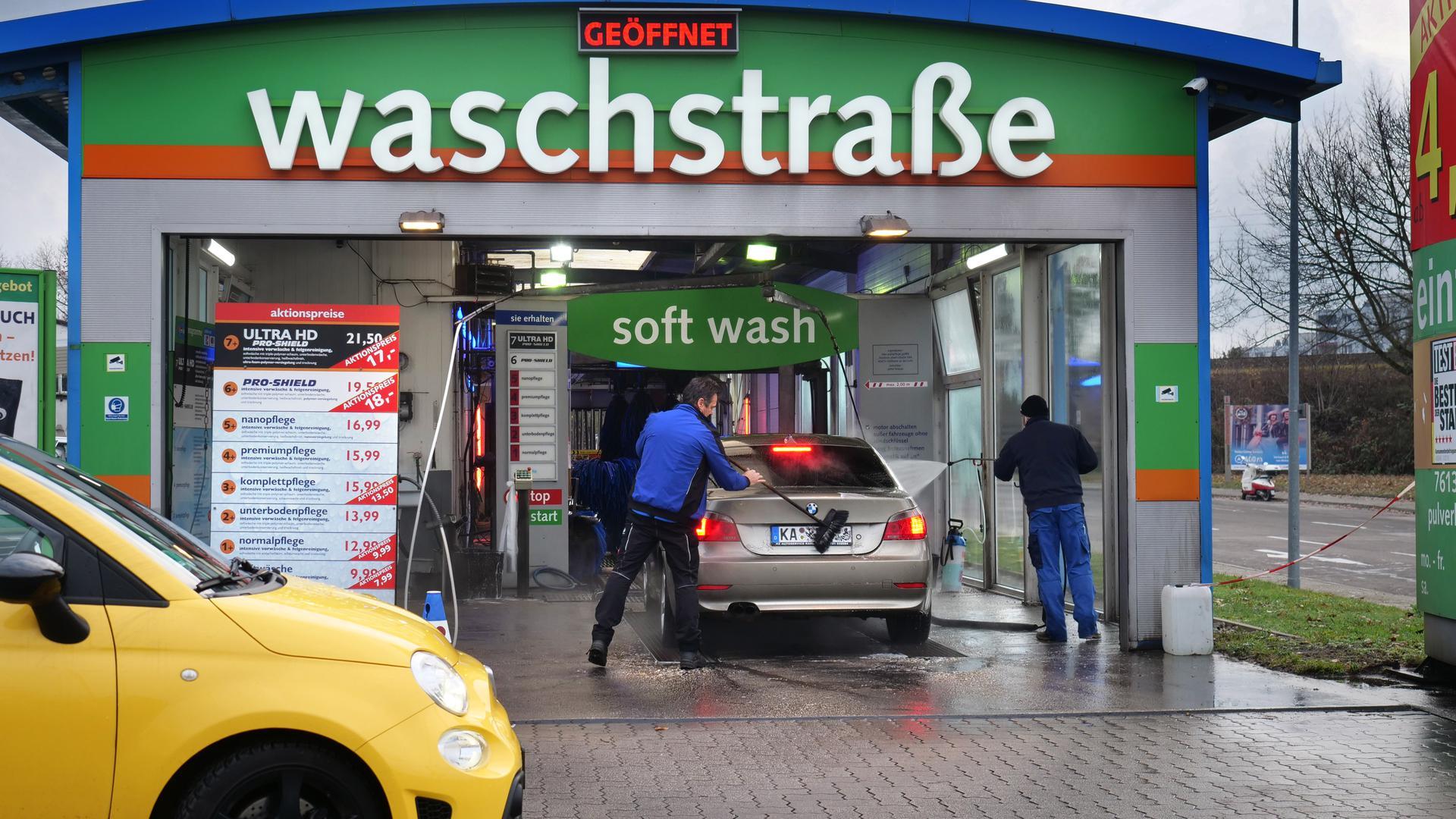 Auto wird in der Waschanlage von zwei Männern geputzt.