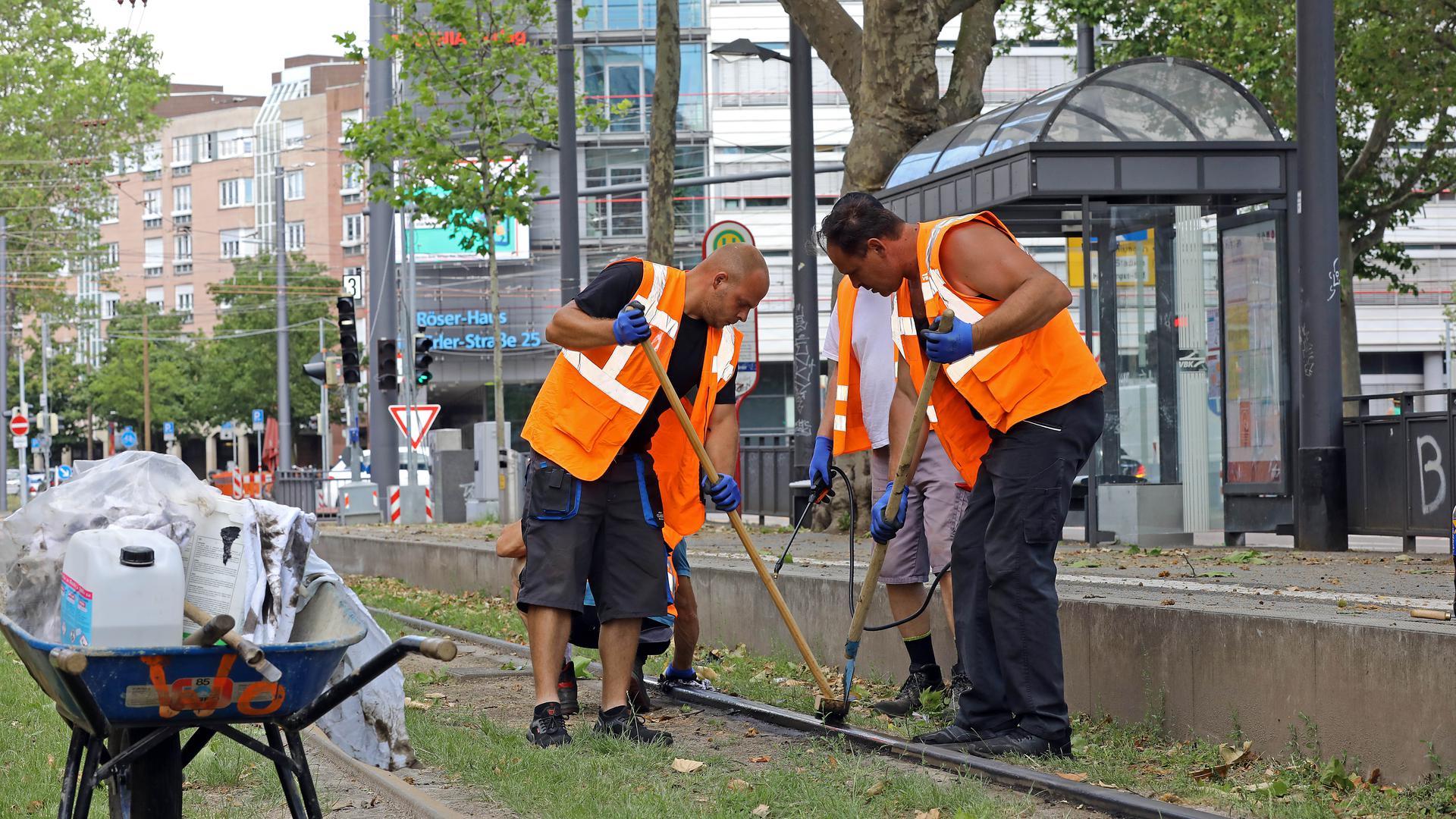 Arbeiter reinigen eine Schiene