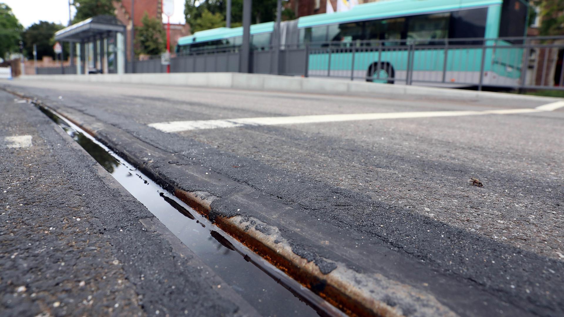 Verschmutzte Gleise im Vordergrund, der Schienenersatzverkehr im Hintergrund