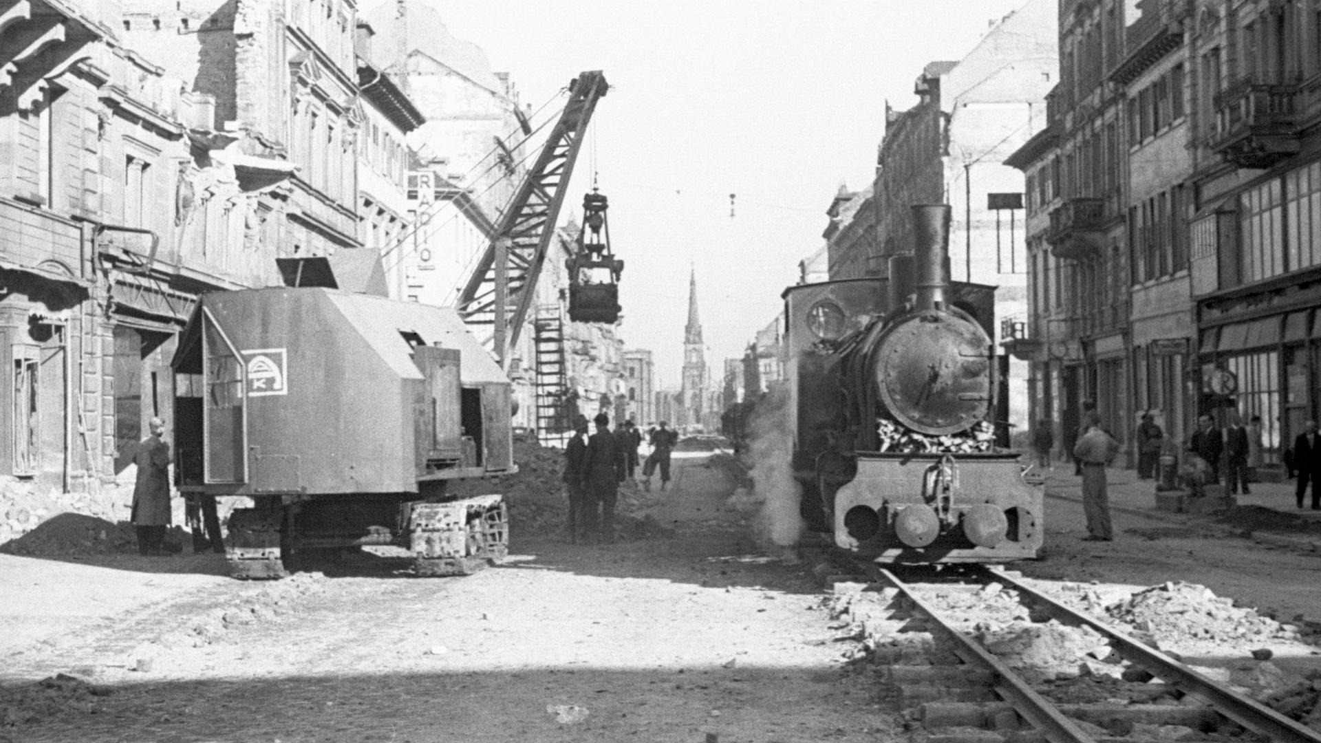 Ein Bagger hebt auf der Karlsruher Kaiserstraße Schutt in die bereitstehenden Loren der Karlsruher Schuttbahn.