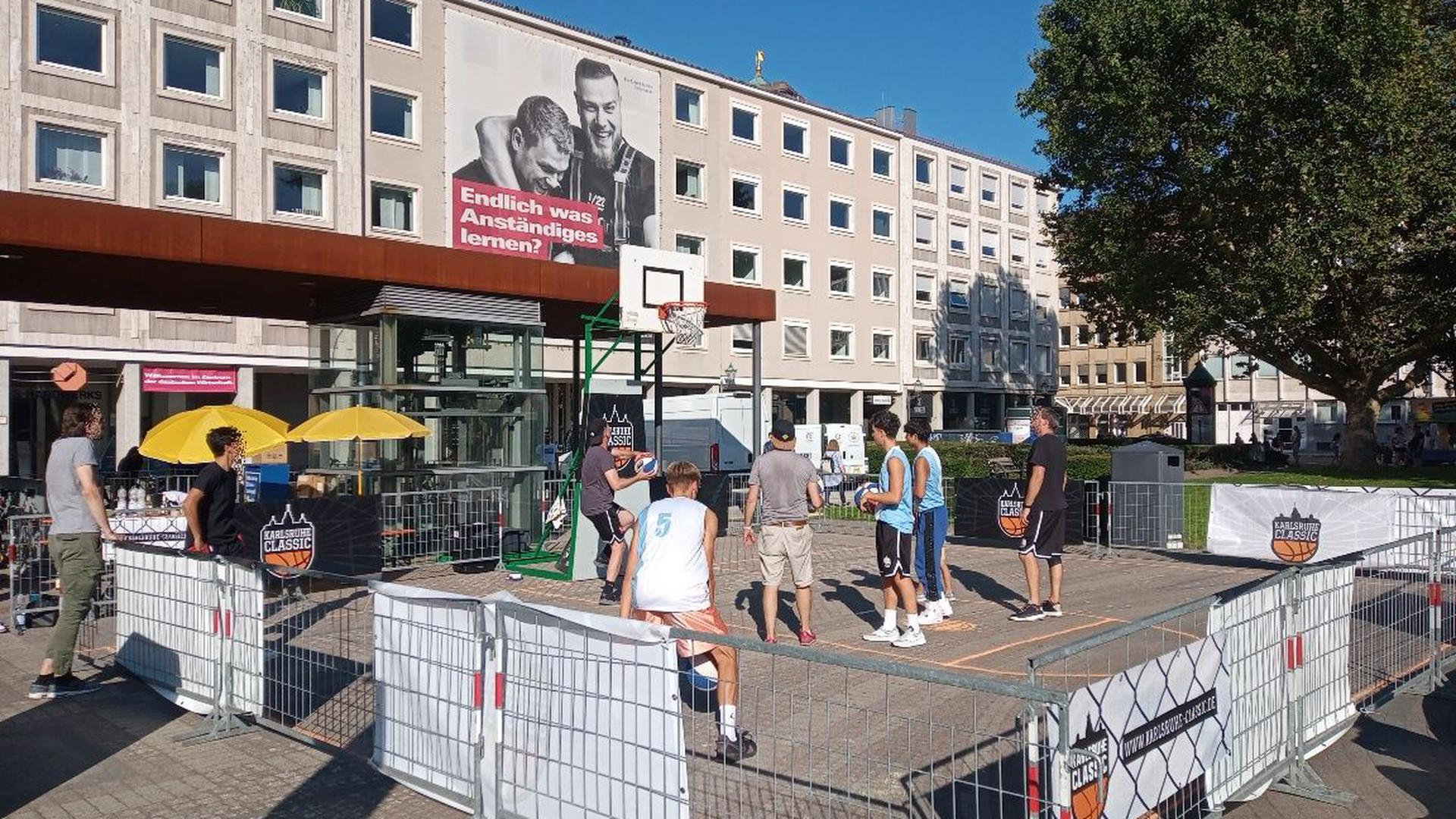 Zu Hip-Hop-Rhythmen und Black Music fliegen blau-weiß-rot gestreifte Basketbälle aus jeder Ecke des mit Absperrgittern abgegrenzten Areals auf den Korb auf dem Karlsruher Friedrichsplatz.