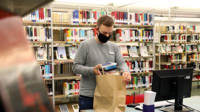 Bibliothekar Jan Roth packt die bestellten Bücher in eine Papiertüte.