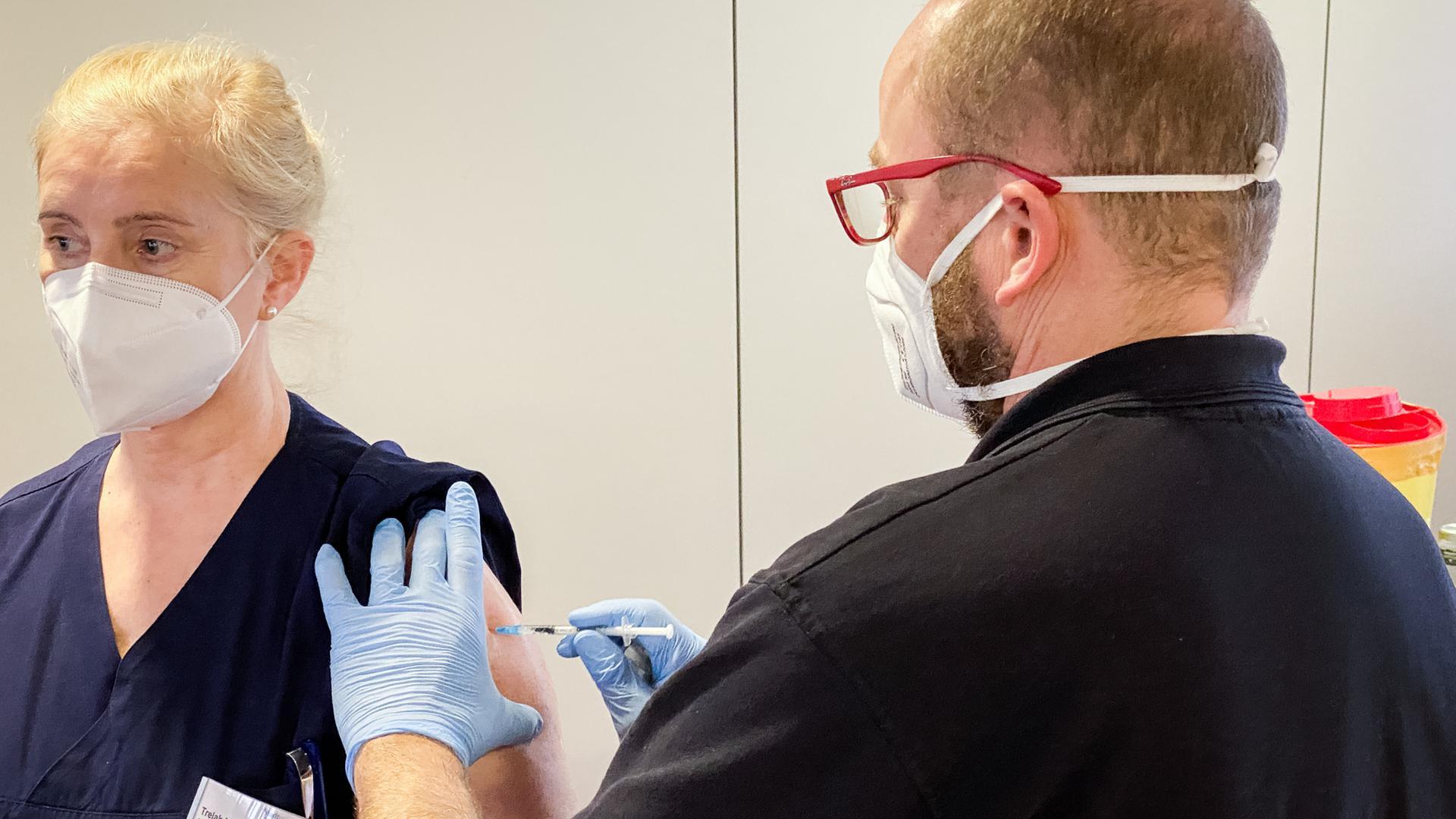 Arzt Christoph Nießner spritzt Mira Trelak den Corona-Impfstoff