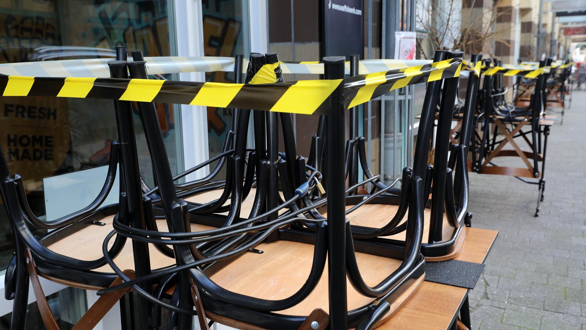 Vor einem Restaurant sind die Stühle auf den Tischen aufgestuhlt und mit Absperrband beklebt.