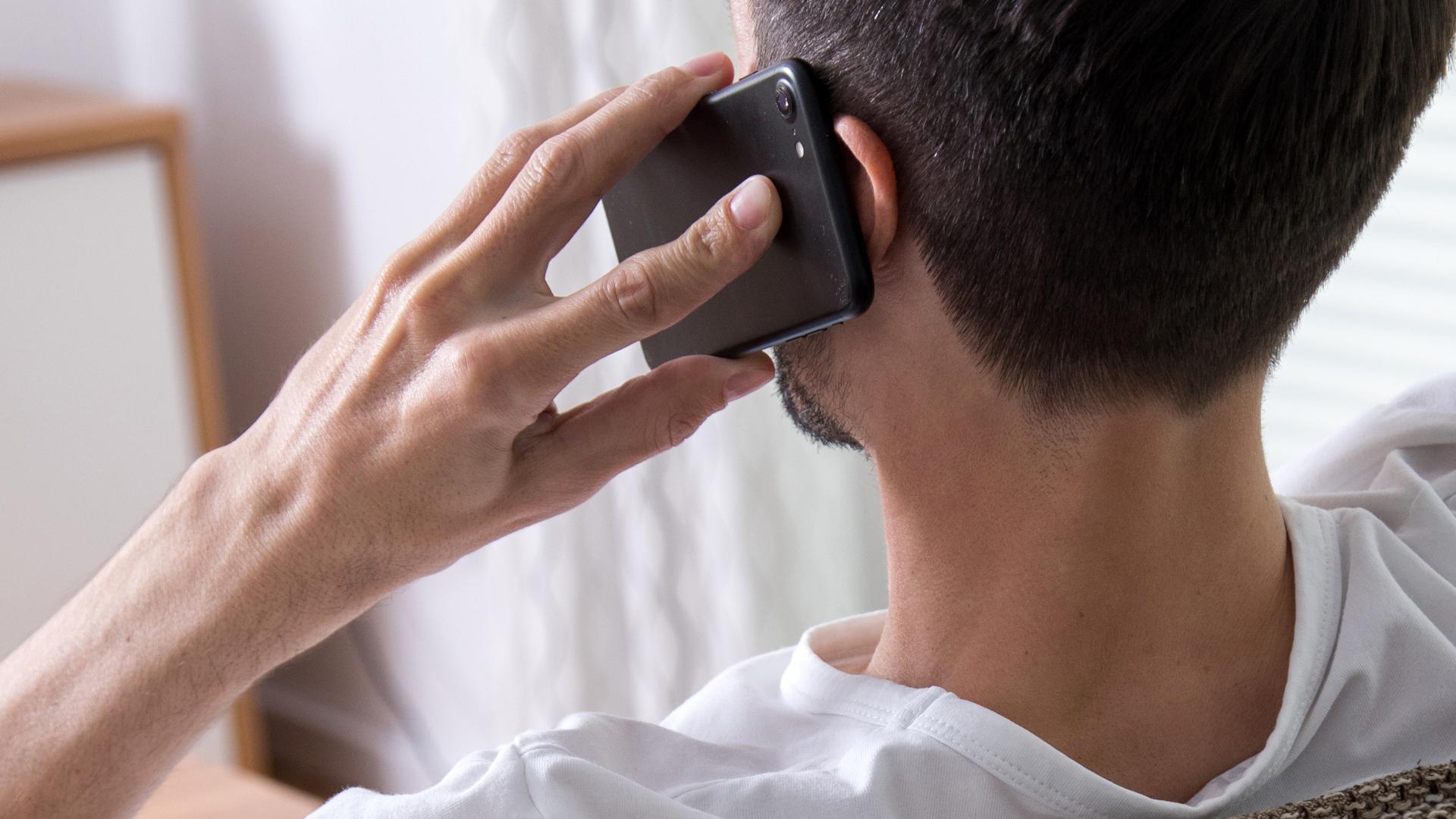 Mann hat ein Handy am Ohr