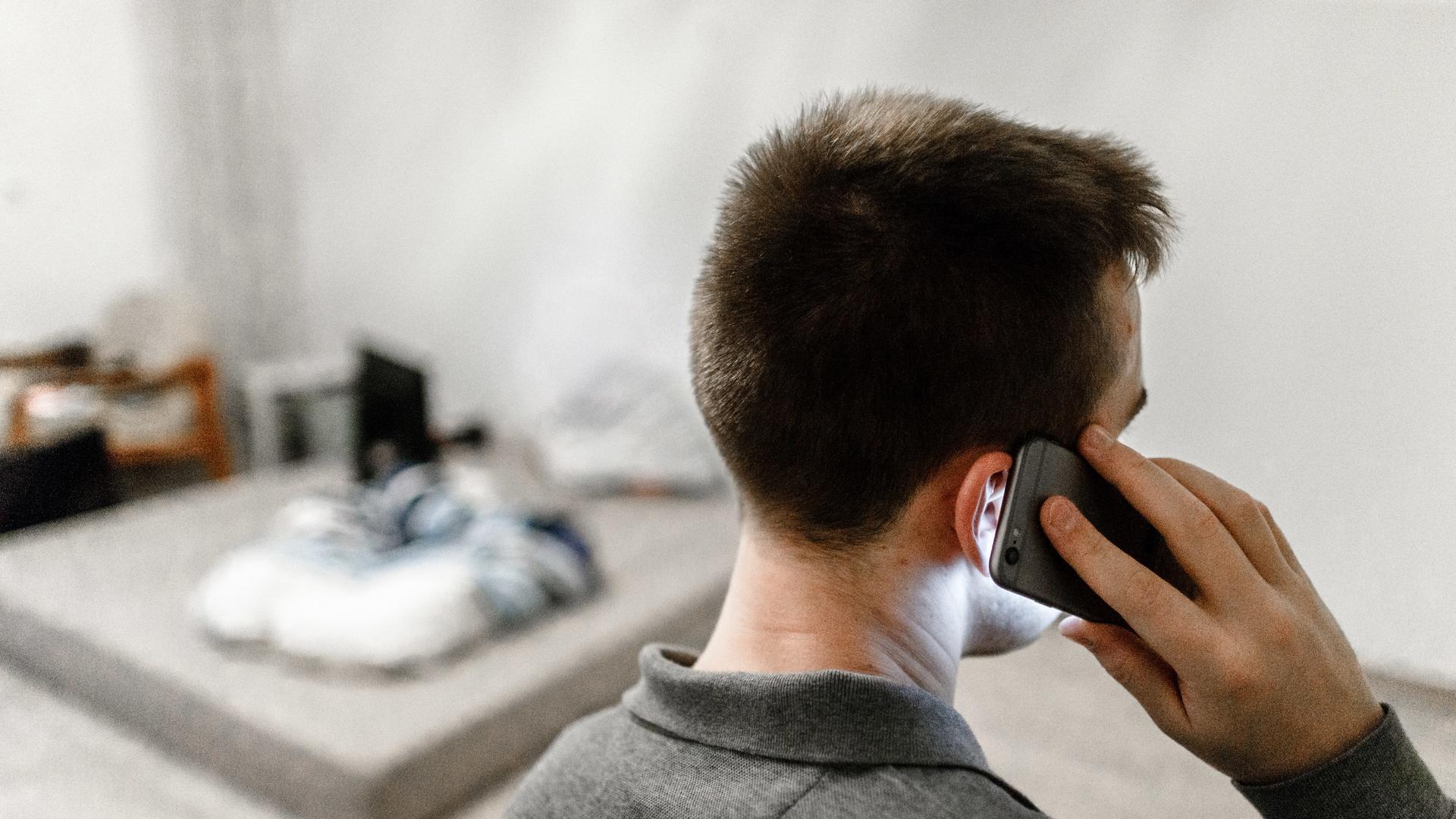 Ein Mann ruft am 23.12.2017 in Hamburg mit seinem Handy bei der Telefonseelsorge an. Foto: Markus Scholz/dpa +++(c) dpa - Bildfunk+++ | Verwendung weltweit